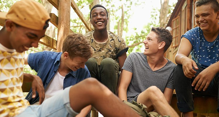 Shot of a group of teen boys hanging out together outside
